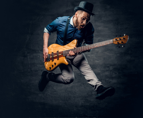 "Featured photo for ""Funk Rock Bass Lessons"" at Knoxville Bass Lessons depicting man dressed in hip clothing with suspenders and cylinder hat jumping high in the air while playing a bass guitar"