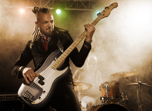 "Featured photo for ""Grunge Rock Bass Lessons"" at Knoxville Bass Lessons depicting bearded man with dreadlocked hair in dark clothing playing bass guitar"